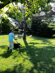 Lavoratore taglia il prato usando un tosa erba a motore
