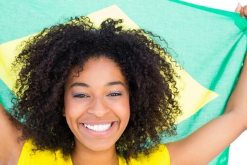 Pretty girl in yellow tshirt holding brazilian flag smiling at c
