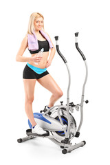 Woman holding water on a cross trainer machine