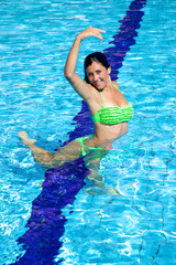 Cute girl playing in the water having fun in swimming pool