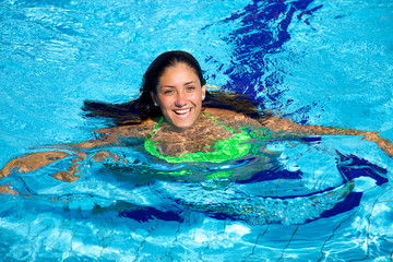 Cute young woman happy smiling in water of swimming pool