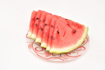 Cut pieces of watermelon on a plate on white background