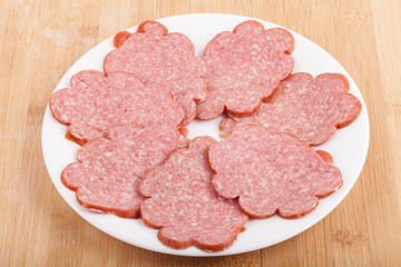sliced ​​sausage on a white plate on wood