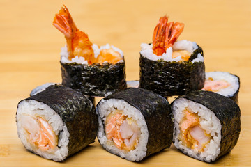 Fresh sushi with ebi tempura shrimps on wooden background