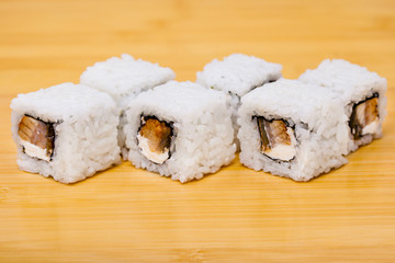 Fresh sushi roll with eel isolated on wooden background