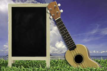 Ukulele with blue sky and Blackboard on green grass