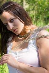 Natural Green Eyed Girl In White Dress With Feather Grass