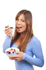 Junge Frau isst Früchtemüsli