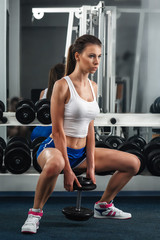 Beautiful young woman during fitness with dumbbells.