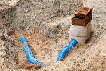Strassenbau - ein neuer Gulli und neue blaue Abwasserrohre