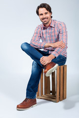 Handsome young man sitting on a wooden box