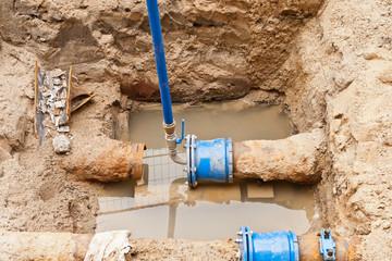 Reparaturarbeiten an einer alten Wasserleitung aus Gusseisen