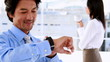 Businessman using his smart watch and smiling