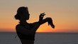 Attractive girl dancing oriental dance at sunset