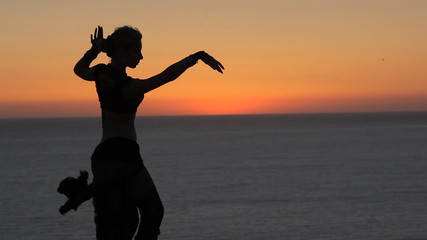 Gorgeous girl dancing oriental dance at sunset