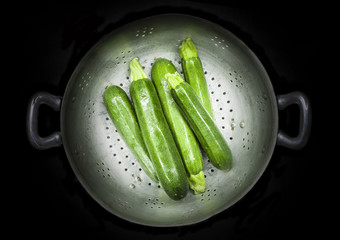 Colander with five courgettes