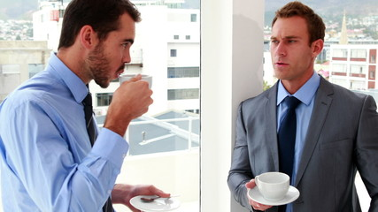 Businessmen chatting and drinking coffee