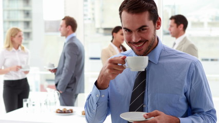 Businessman standing and drinking a coffee