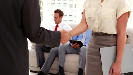 Business people shaking hands in front of interview line