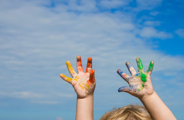 Hands of baby paint against blue sky