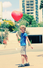 cute 6 years old boy holding red balloon