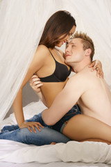 Loving couple sitting on a bed in a close embrace