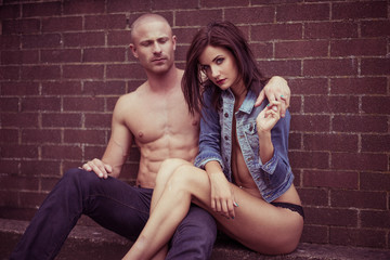 Sweet couple sitting in front of brick wall