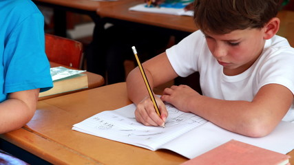 Little boy drawing in notepad in classroom