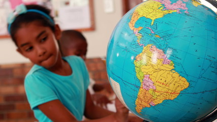 Little girl looking at globe and writing in classroom