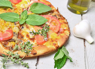 Pizza with ham, pepper , olives and fresh herbs, thyme