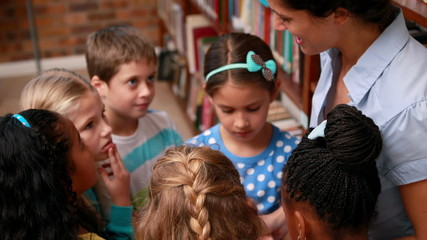 Pupils talking with their teacher in the library