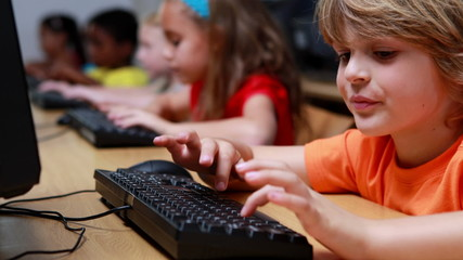 Little boy smiling at camera during computer class