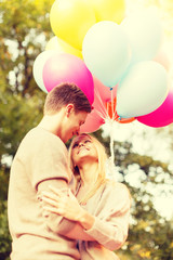 smiling couple with colorful balloons in park