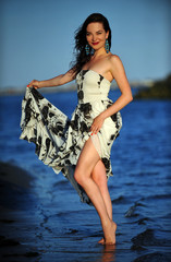 Gorgeous young model in luxury dress posing at the beach.