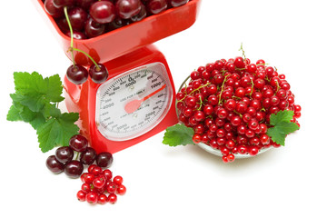 red currant berries, cherries and kitchen scale on white backgro
