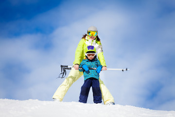 Mother and kid in masks standing with ski polls