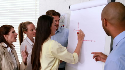 Casual business team watching colleague draw graph
