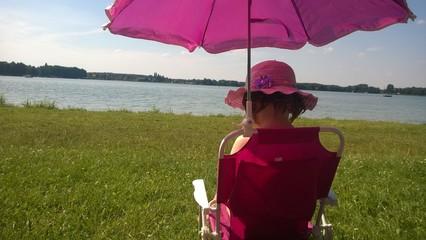kleines Mädchen sitzt am See