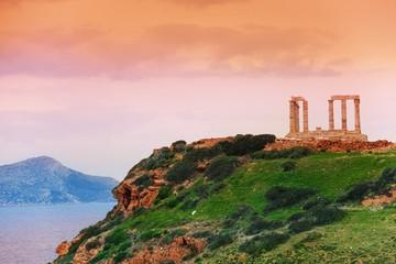 Temple of Poseidon on green hill near sea, Greece