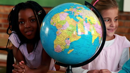 Cute pupils smiling around a globe in classroom