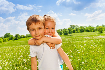 Pretty girl embraces boy on a meadow
