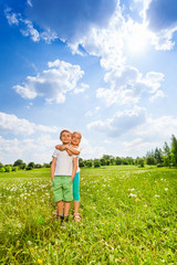 Two children stand together on a meadow