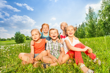 Group of children laugh sitting on a grass