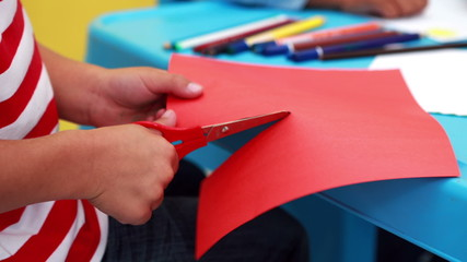 Cute little boy cutting paper shapes classroom