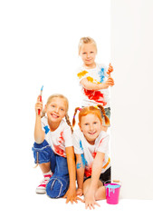 Three little girls in painted shirts smile