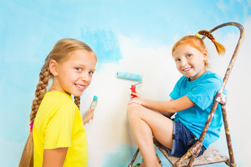 Two smiling girls with blue wall on a background