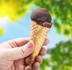 hand holding ice cream with chocolate on a background of nature