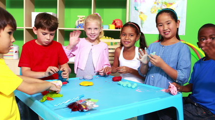Cute classmates playing with clay and waving at camera