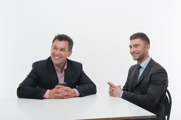 Two colleagues business partners sitting at desk isolated on whi