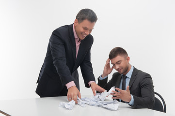 Boss angry with young employee sitting at desk